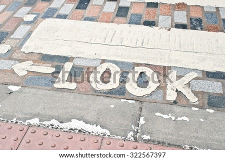 The word look painted on an old cobblestone road at a pedestrian crossing - stock photo