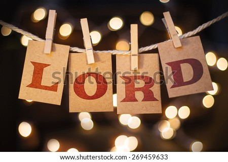 The word LORD spelled out on clothespin clipped cards in front of glowing lights. - stock photo