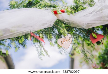 """The word """"Love"""" on a wooden heart. The inscription hanging on the arch of green branches of pine tree. decor for party. wooden word love. - stock photo"""