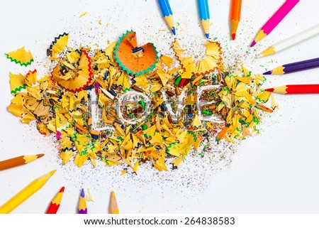 The word LOVE on the background from colored pencil shavings - stock photo