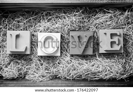 The word Love spelled out in big block letters in a wooden gift box filled with raffia  in stunning black and white - stock photo