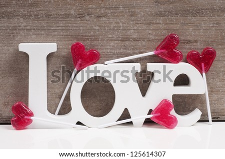 The word Love with heart shaped lollipops. Valentine card design - stock photo