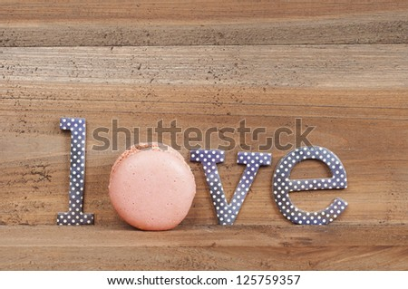 The word Love with macaroons on wooden background - stock photo