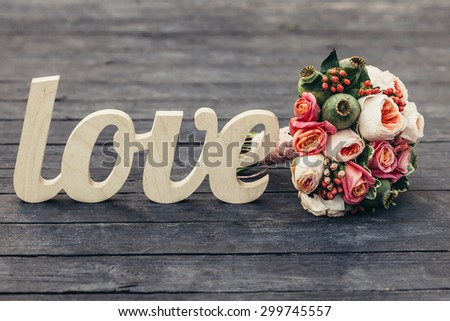 The word love with  wedding bouquet on wooden background - stock photo