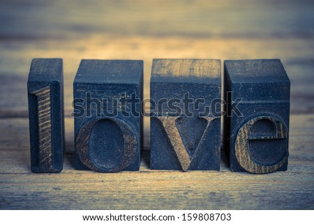 The word LOVE wriiten with vintage printing blooks over old wood background - stock photo