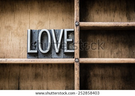 "The word ""LOVE"" written in vintage metal letterpress type sitting in a wooden drawer. - stock photo"