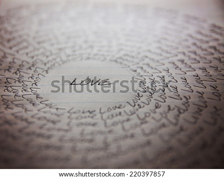 the word love written on a lined piece of school paper in ink with a vignette and a circle of love (very shallow depth of field - focus on the bottom of the word love) - stock photo