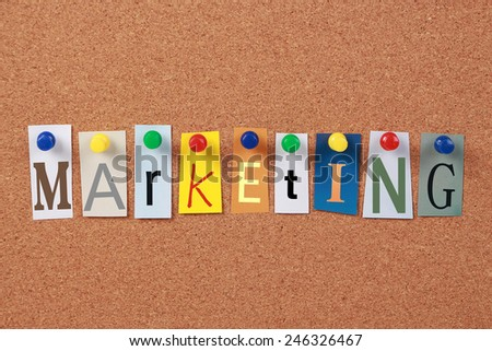 The word Marketing in cut out magazine letters pinned to a cork board. - stock photo