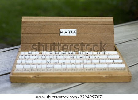 """the word """"maybe"""" on an old school letter box - stock photo"""