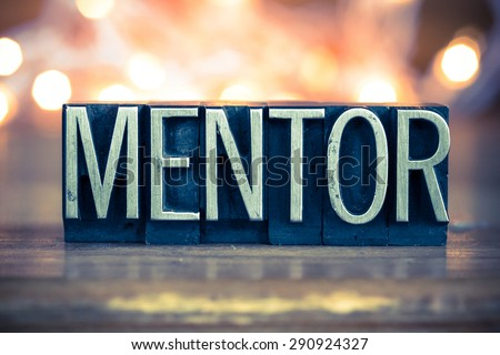 The word MENTOR written in vintage metal letterpress type on a soft backlit background. - stock photo