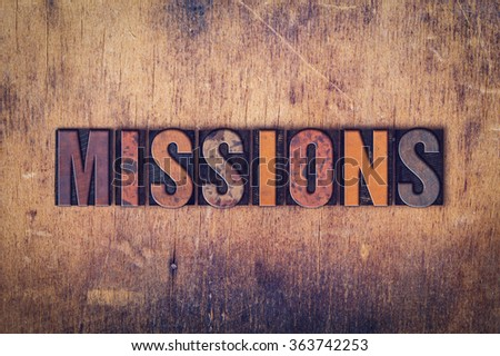 """The word """"Missions"""" written in dirty vintage letterpress type on a aged wooden background. - stock photo"""