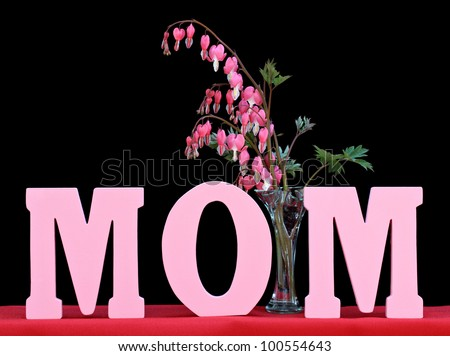 The word MOM isolated on black with a vase of beautiful bleeding hearts.  Perfect for Mother's Day or mom's birthday. - stock photo
