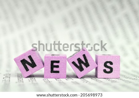 the word news on pink cubes on a newspaper - stock photo