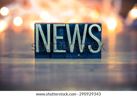 The word NEWS written in vintage metal letterpress type on a soft backlit background. - stock photo