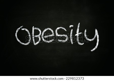 The word Obesity written with chalk on blackboard - stock photo