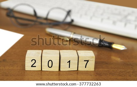 The word 2017 on wood stamp stacking on desk with keyboard, vintage retro image style - stock photo