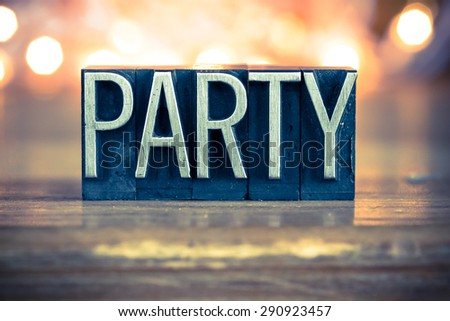 The word PARTY written in vintage metal letterpress type on a soft backlit background. - stock photo