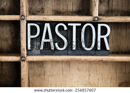 "The word ""PASTOR"" written in vintage metal letterpress type in a wooden drawer with dividers. - stock photo"