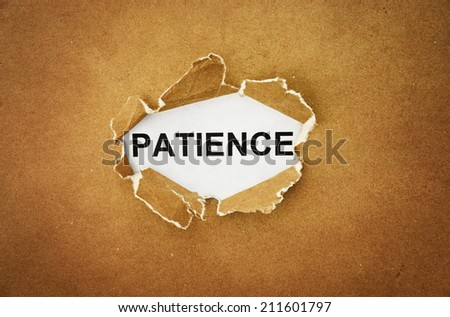 "the word ""patience"" in the hole of brown paper - stock photo"
