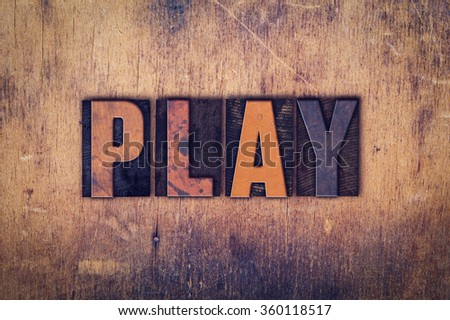 """The word """"Play"""" written in dirty vintage letterpress type on a aged wooden background. - stock photo"""