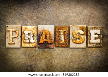 "The word ""PRAISE"" written in rusty metal letterpress type on an old aged leather background. - stock photo"