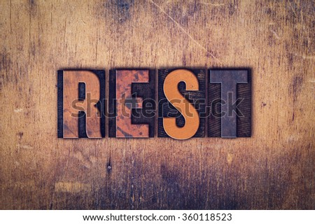 """The word """"Rest"""" written in dirty vintage letterpress type on a aged wooden background. - stock photo"""