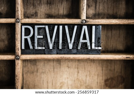 "The word ""REVIVAL"" written in vintage metal letterpress type in a wooden drawer with dividers. - stock photo"
