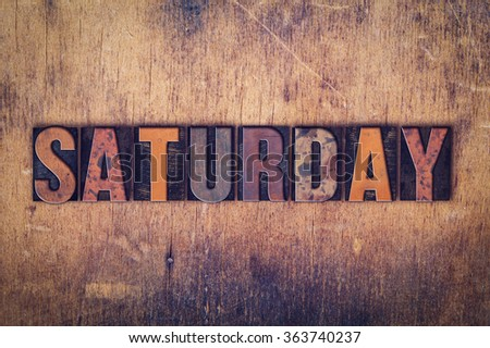 """The word """"Saturday"""" written in dirty vintage letterpress type on a aged wooden background. - stock photo"""