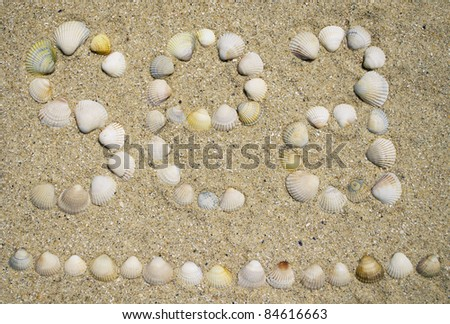 """The word """"sea"""", lined with seashells on the sand - stock photo"""
