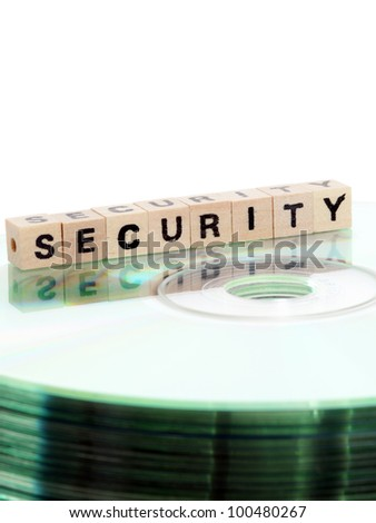 The word security written in wooden letters standing on a computer-CD - stock photo