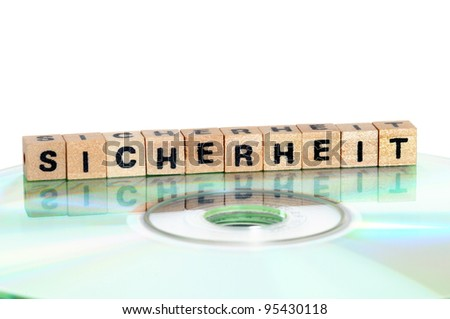 The word Sicherheit ( = security) written in wooden letters standing on a computer-CD - stock photo
