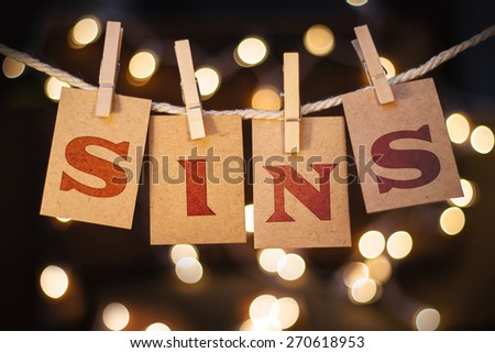 The word SINS printed on clothespin clipped cards in front of defocused glowing lights. - stock photo