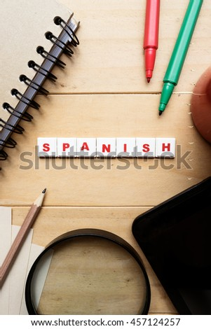 "the word ""Spanish"" spelled using letter tiles on wooden background - stock photo"