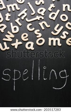 The word Spelling written in white chalk on a blackboard underneath random wooden letters of the alphabet - stock photo