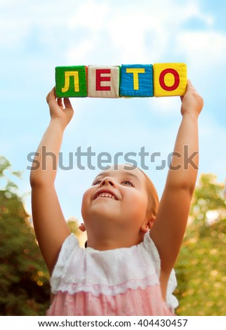 "The word ""Summer"" in Russian in the hands of the child of soft cubes in the sky - stock photo"