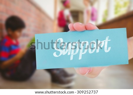 The word support and hand showing card against schoolboy with friends in background at school corridor - stock photo