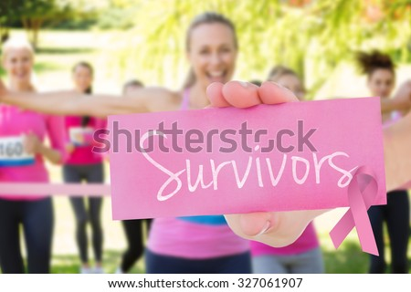 The word survivors and young woman holding blank card against smiling women running for breast cancer awareness - stock photo