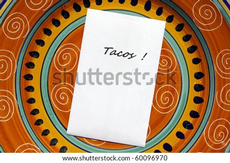 The word TACOS! printed on white paper with copy space on top of colorful Mexican style plate. - stock photo