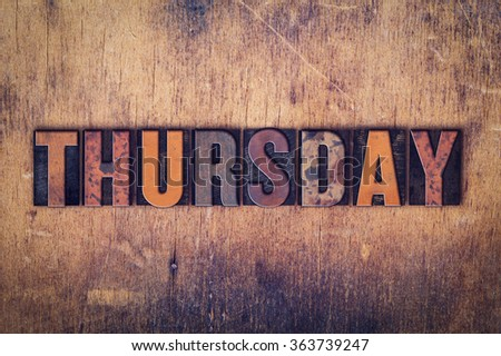 """The word """"Thursday"""" written in dirty vintage letterpress type on a aged wooden background. - stock photo"""