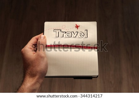 The word travel sketched on a open notebook and held by a male traveler, dreaming about all the foreign destinations he wants to visit across the globe.   - stock photo