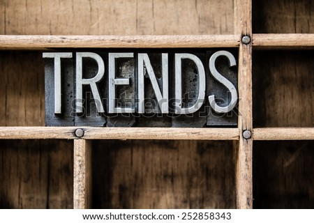 """The word """"TRENDS"""" written in vintage metal letterpress type sitting in a wooden drawer. - stock photo"""