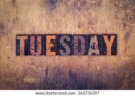 """The word """"Tuesday"""" written in dirty vintage letterpress type on a aged wooden background. - stock photo"""