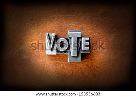 The word vote made from vintage lead letterpress type on a leather background. - stock photo