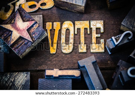 The word VOTE written in rusted metal letters surrounded by vintage wooden and metal letterpress type. - stock photo