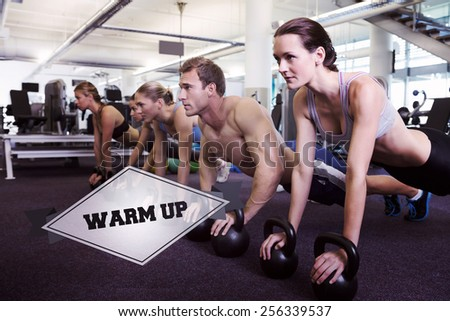 The word warm up and fitness class in plank position with kettlebells against badge - stock photo