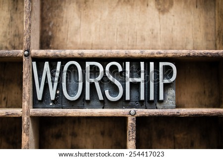 "The word ""WORSHIP"" written in vintage metal letterpress type in a wooden drawer with dividers. - stock photo"
