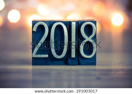 The word 2018 written in vintage metal letterpress type on a soft backlit background. - stock photo