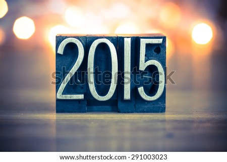 The word 2015 written in vintage metal letterpress type on a soft backlit background. - stock photo