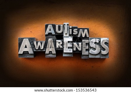 The words Autism Awareness made from vintage lead letterpress type on a leather background. - stock photo