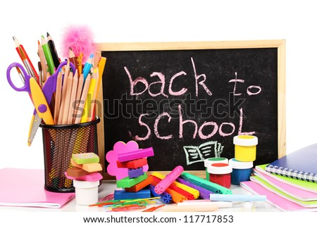 The words 'Back to School' written in chalk on the small school desk with various school supplies close-up isolated on white - stock photo
